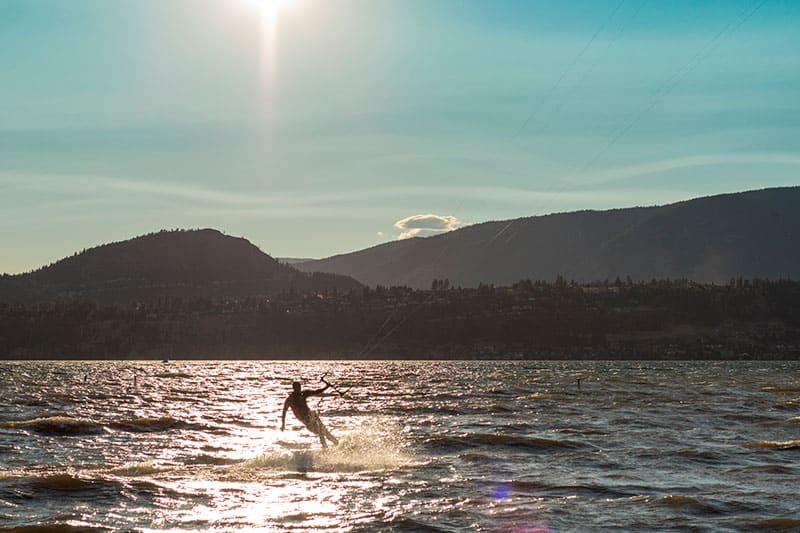 kelowna sunset shot of the okanagan lake in which a man is kiteboarding