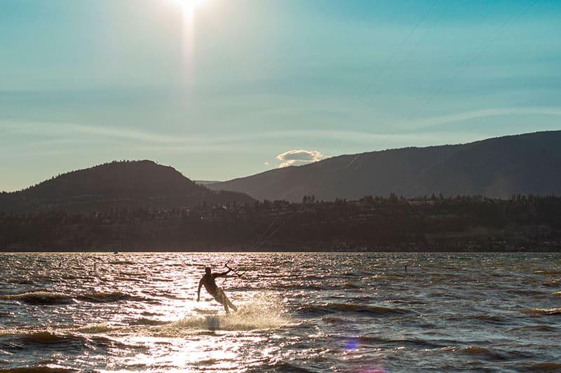 kelowna sunset shot of the okanagan lake in which a man is kiteboarding