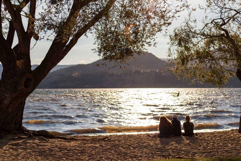 kelowna sunset beach shot of three family members sitting together besides a massive tree
